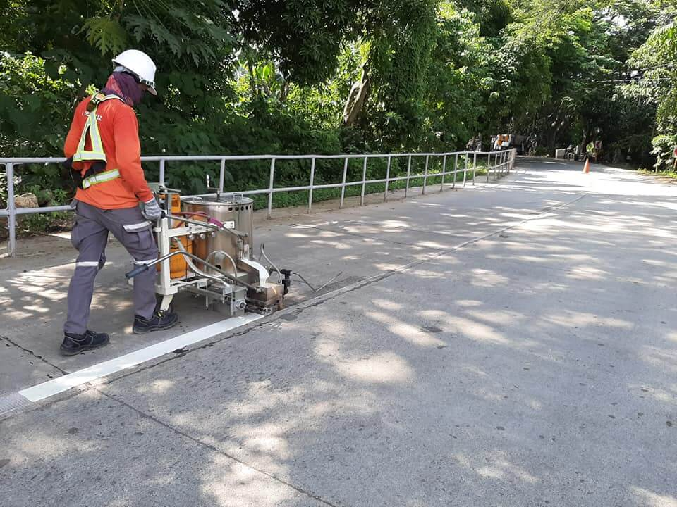Road contractor applying white road marking paint